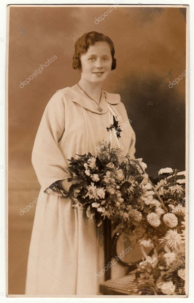 f65dc703b94 Black   white studio portrait.– stock image. Vintage photo shows a bride  with bouquet poses in a photography studio. Photo with sepia