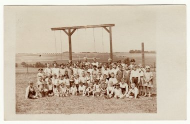 Vintage photo shows a group of children outdoors. Horizontal bar for rope- climbing is on the background.  Black & white photo.