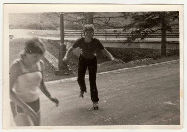 Retro photo shows girl who rides on roller skates . Black & white vintage photography.