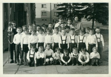 Retro photo shows small pupils and they female teachers (schoolmistresses) pose for photograper outside. Vintage black & white photography.