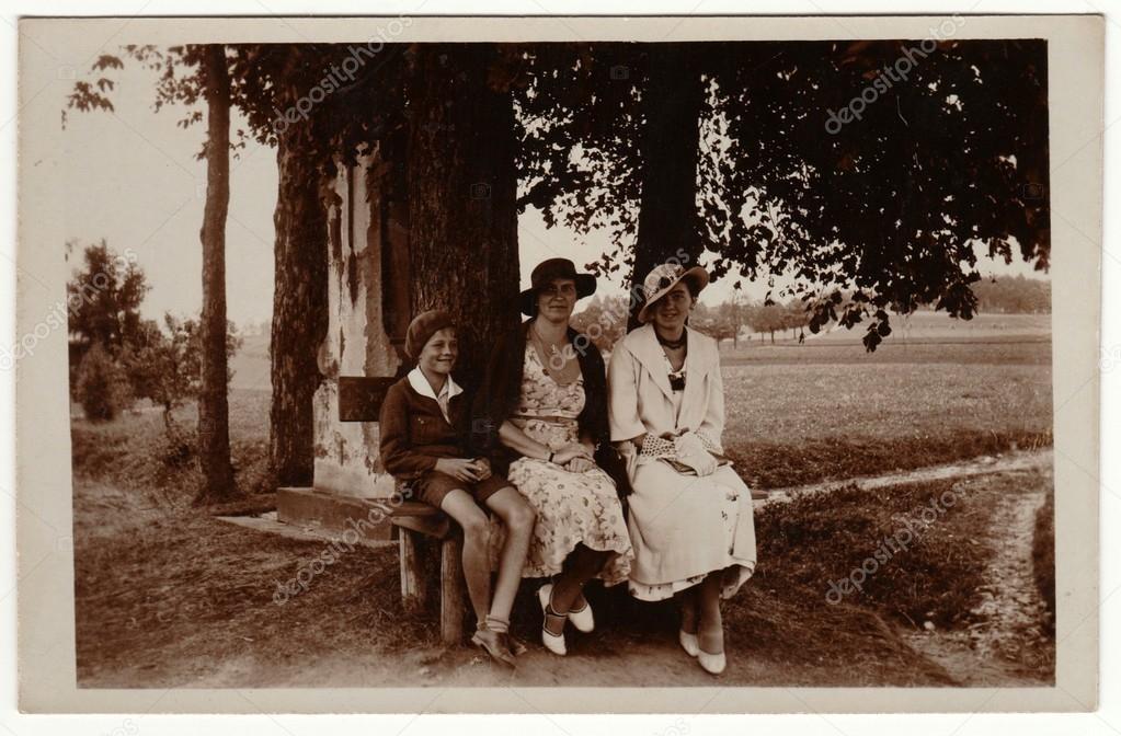 c207e36dda Archiwalne zdjęcie pokazuje kobiety nosić eleganckie sukienki i kobiet  parisisol dużym rondem kapelusza. Kobieta i chłopiec pozować na zewnątrz i  siedzieć ...