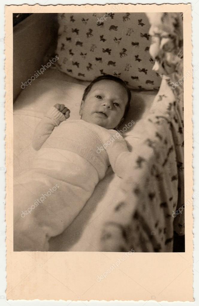 Foto de época muestra a lindo pequeño bebé en la cuna (cuna, cama de ...