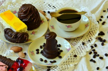Desserts with cup of coffee, coffee beans and almonds on white tablecloth.