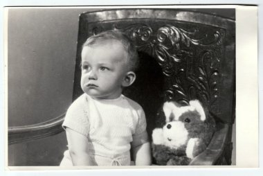 Retro photo of a small boy with teddy bear.  Portrait photo was taken in photo studio, circa 1972.