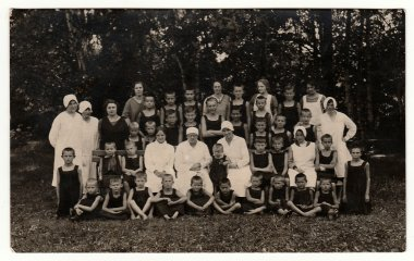 Vintage photo shows a group of boys and nurses in nature. Photo was taken in sanatorium, circa 1940s.