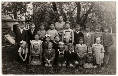 Vintage photo shows classmates (about 10 years old) with teacher