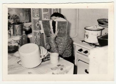 Vintage photo shows a small boy covers up his face by book.