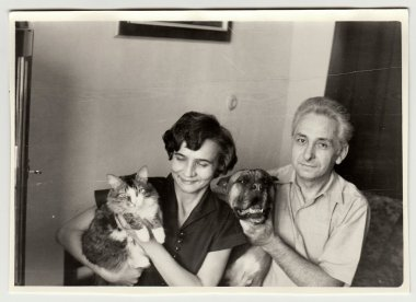 Vintage photo shows woman cradles cat and man holds dog.