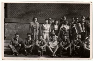 A vintage photo shows group of people, one of them plays the button accordion. Antique black & white photo.
