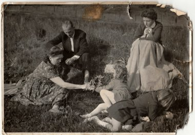 Vintage photo shows family on meadow.