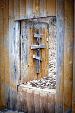 The cross on a wooden door. Entrance to the monastery