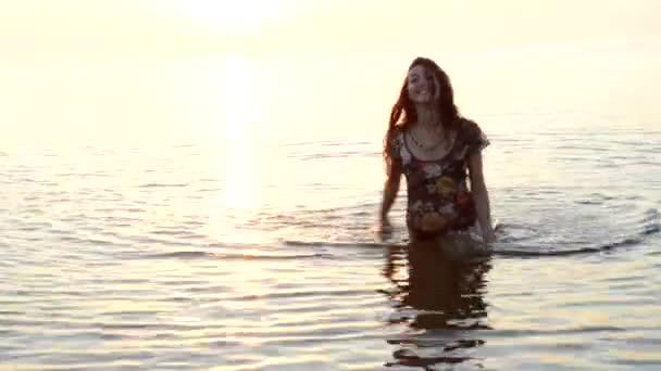dívka stojící v moři a s úsměvem
