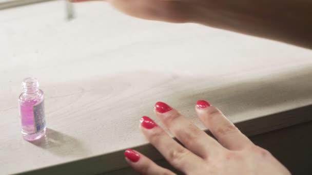 mladá evropská dívka si lakuje nehty čistým lakem