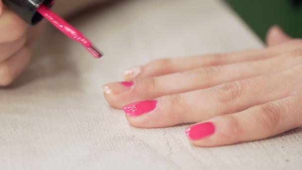 ein junges europäisches Mädchen lackiert ihre Nägel mit rosa Nagellack