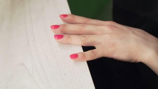 mladá evropská dívka maluje nehty růžovým lakem na nehty