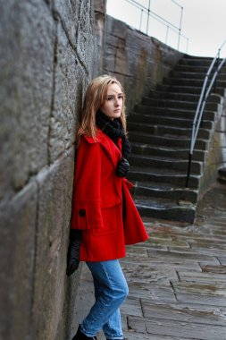 Woman in a red coat leaning on an old stone