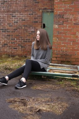 Pretty young teenage girl sitting on some old doors