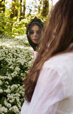 Beautiful girl looking into a mirror