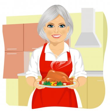 Sweet grandmother in red apron cooking traditional thanksgiving turkey