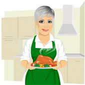 Sweet grandmother in green apron cooking traditional thanksgiving turkey