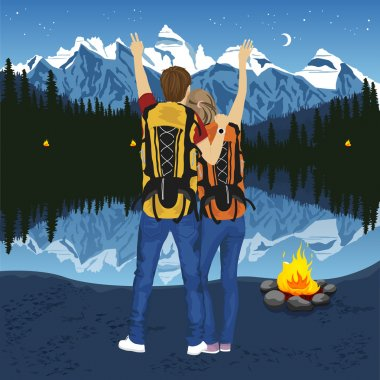 young couple of hikers with hands up enjoying mountain lake at night near capmfire