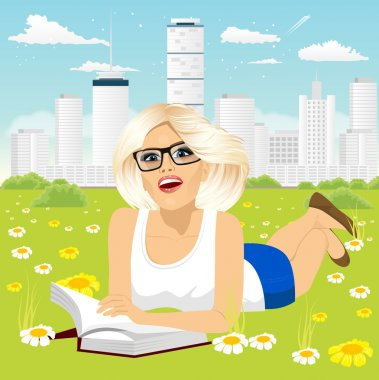 Woman lying down on grass reading book