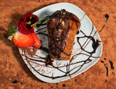 Neapolitan dessert  decorated with chocolate cream,fresh strawberry,pansy and cocoa powder.