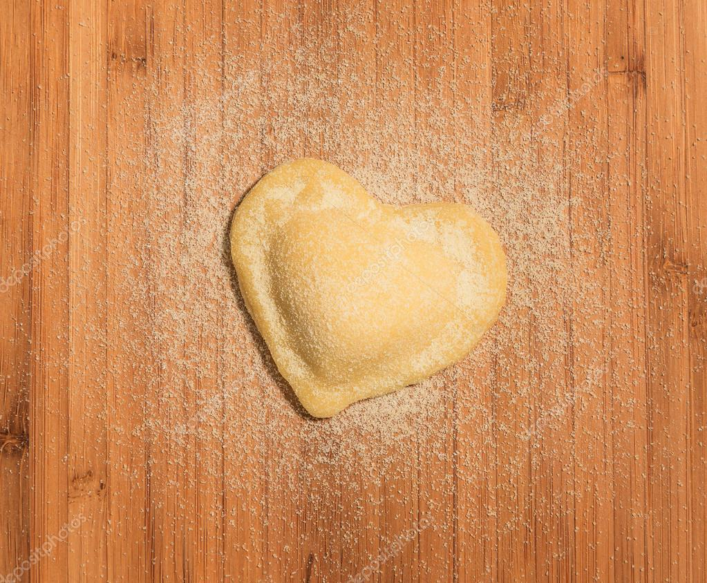 Heart-shaped,homemade single raviolo placed on a wooden table.