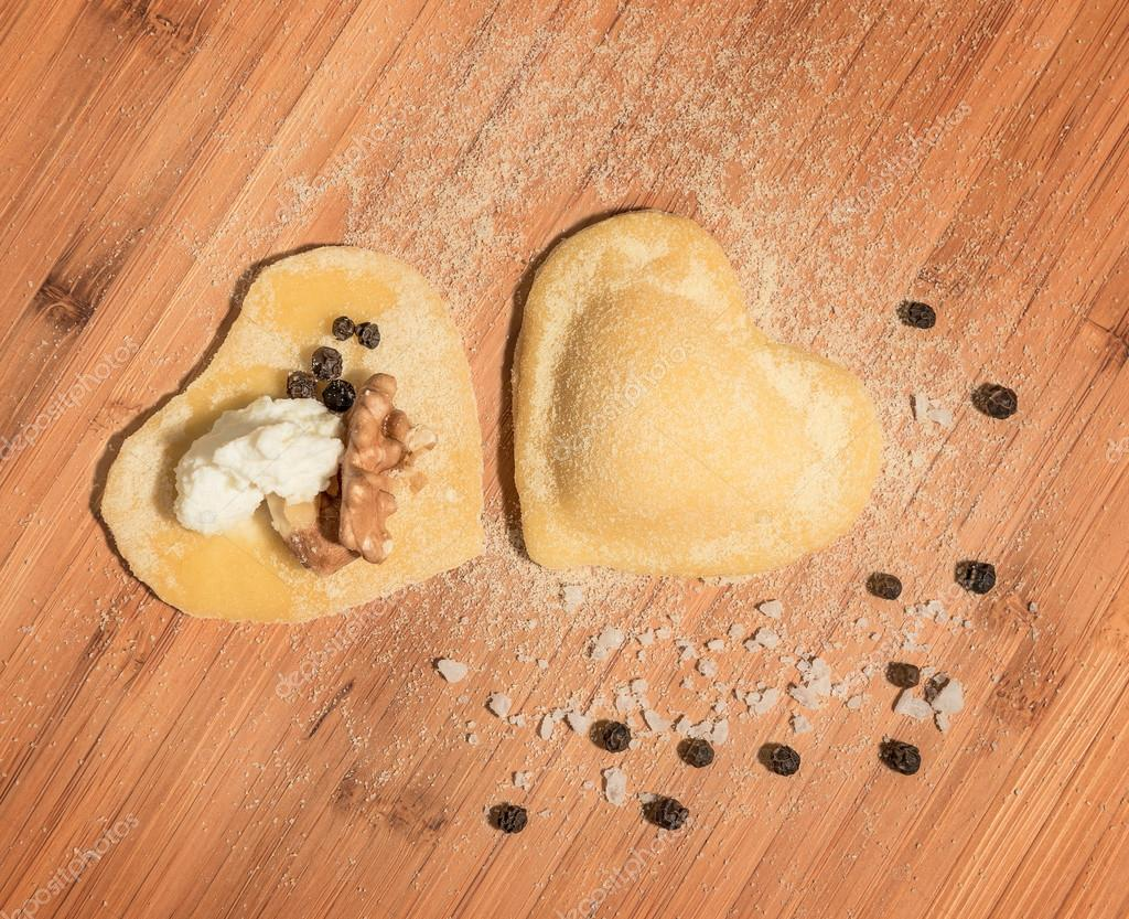 Two raw homemade ravioli ,open and closed,in the shape of heart,sprinkled with flour and placed on a wooden table.