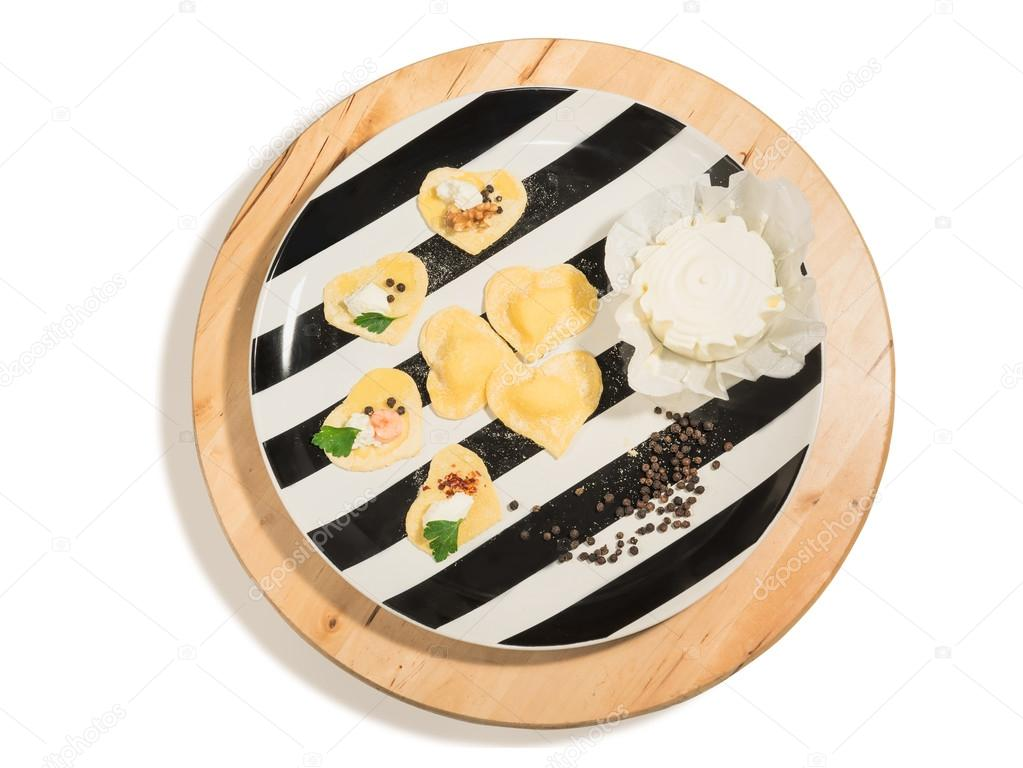 Black and white dish with handmade ravioli in the shape of heart,open and closed,fresh cheese and  few grains of black pepper,placed on a round centerpiece of wood.