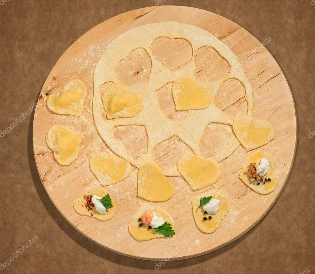 Homemade ravioli in the shape of heart,open and closed, placed on a round centerpiece of wood.