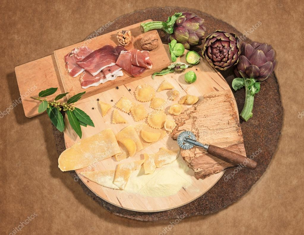 Homemade fresh ravioli with prosciutto,walnuts and artichoke,paced on a rustic round centerpiece.