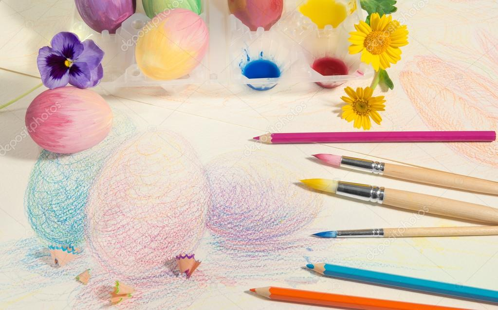Easter hand-painted eggs with colored pencils,watercolors and spring flowers ,arranged on colored drawing.