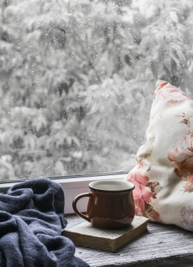 Coffee mug, book, pillows and a plaid on the light wooden surface against window with rainy day view. Vintage style. The concept of homeliness and comfort