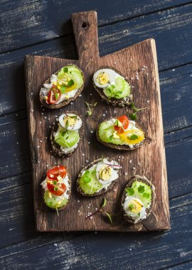 Sandwiches with soft cheese, quail eggs, cherry tomatoes and celery. Delicious healthy snack or Breakfast. On a wooden rustic board