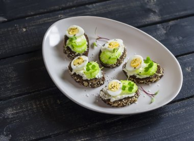 Open sandwiches with cream cheese, quail eggs and celery. Delicious healthy snack or breakfas