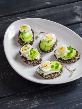 Open sandwiches with cream cheese, quail eggs and celery. Delicious healthy snack or breakfast
