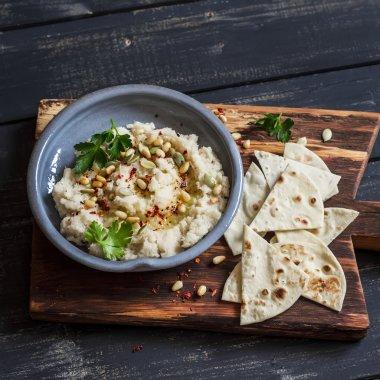 Healthy vegan cauliflower hummus and homemade tortilla on a dark rustic cutting board on a dark background. Delicious healthy snack