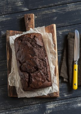 Chocolate cake on a rustic wooden cutting board on dark wooden background