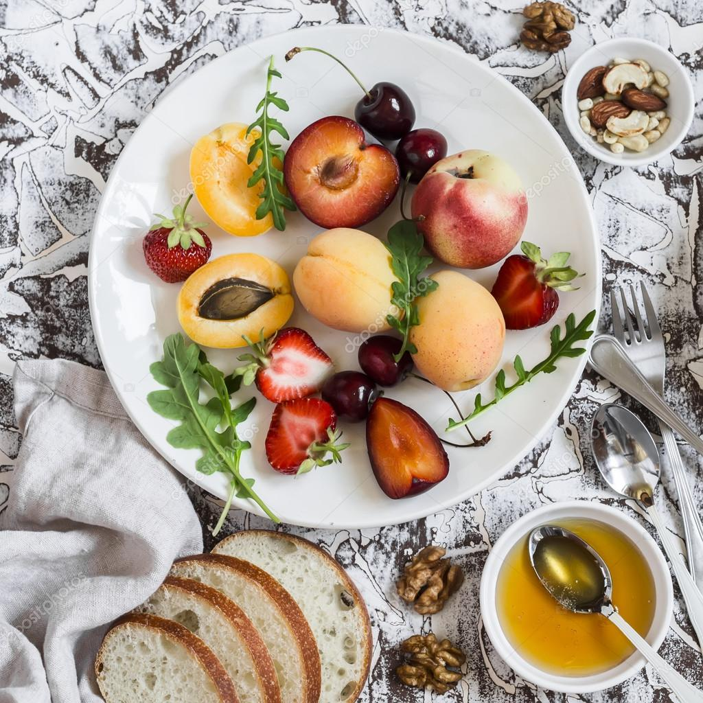 Summer fruits - apricots, peaches, plums, cherries, strawberries and  honey, walnuts on a light stone background
