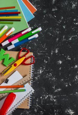 School accessories on a dark background. Top view, free space for text