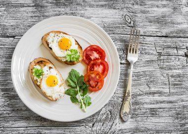 Toast with soft cheese and quail eggs on a white plate