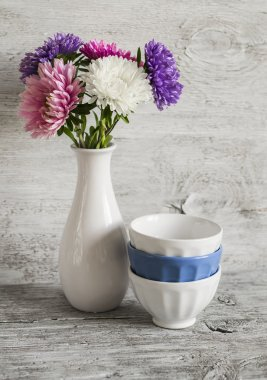 autumn flowers asters in a white vase and ceramic bowl on a light wooden surface