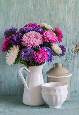 flowers asters in a white enameled pitcher and vintage crockery - ceramic bowl and enameled jar, on a blue wooden background.