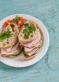 sendvič s celozrnné pečivo, okurkou a šunkou na bílé plotně
