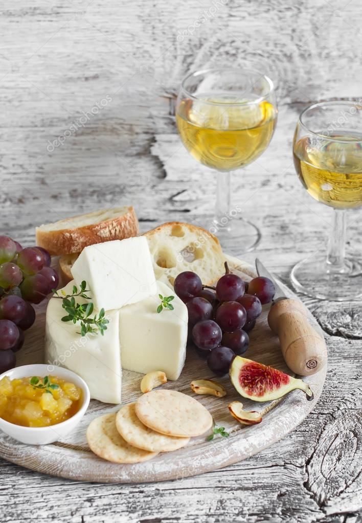 delicious appetizer to wine - ham, cheese, grapes, crackers, figs, nuts, jam, served on a light wooden board, and two glasses with white wine