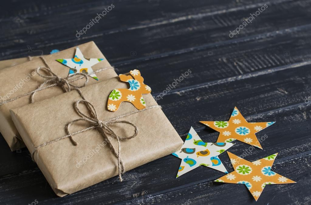 Christmas gifts in kraft paper with a homemade tag on a dark wooden surface.