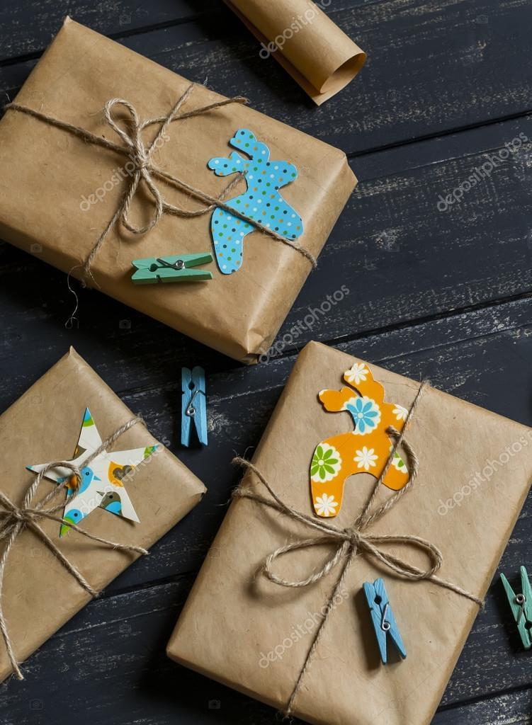 Selbstgemachte Weihnachtsgeschenke in Kraftpapier auf dunklen ...