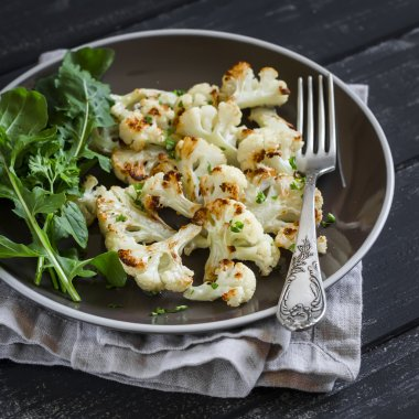 roasted cauliflower and fresh green salad on a brown plate on a dark wooden background