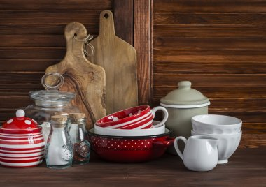 Rustic kitchen still life. Olive cutting board,  jar of flour,  bowls, pan, enamelled  jar,  gravy boat. On a dark brown wooden table. Vintage and rustic style